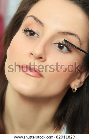 Young beautiful woman making up at home.