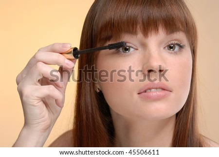 Young beautiful woman making up eyelashes on yellow