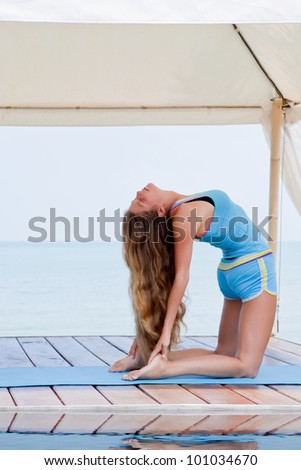 Young beautiful woman making yoga on the beach