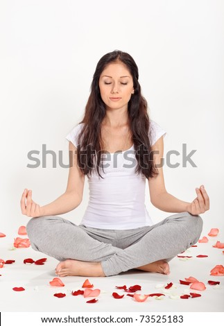 Young beautiful woman meditating in lotus pose sitting on the floor covered with rose petals