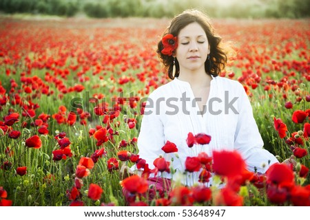 Young beautiful woman meditating in spring field