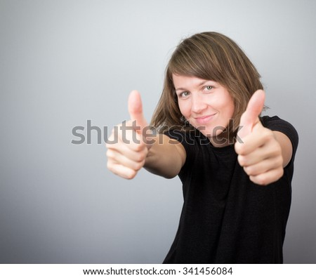 Young beautiful woman model female studio thumbs up funny humoristic cheerful happy smile. #341456084