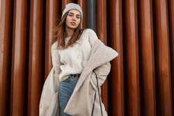 Young beautiful woman model in stylish youth warm outerwear posing near a modern wall on the street. Attractive girl in fashionable clothes is standing in the city. New spring collection. Style.