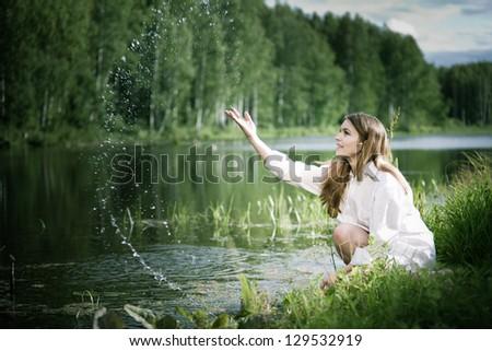Young beautiful woman near water smiling