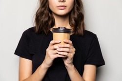 Young beautiful woman offers white cup of coffee isolated on gray background