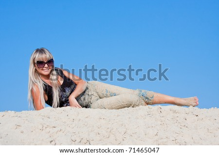 young beautiful woman  on a sand-pit  on a background blue sky