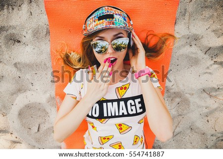 young beautiful woman on beach on orange yoga mat, listening to music on headphones, hipster sport swag style, denim shorts, t-shirt, cap, sunglasses, summer weekend, emotion, positive