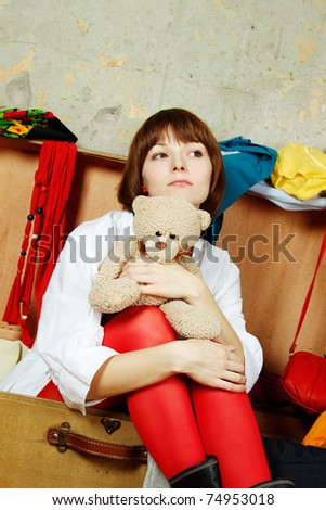 Young beautiful woman on the background of a concrete wall system sits in a big old-fashioned suitcase filled with clothes. Hugs a toy teddy