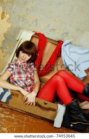 Young beautiful woman on the background of a concrete wall system sits in a big old-fashioned suitcase filled with clothes.