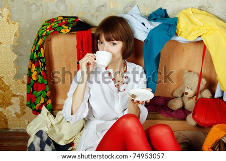 Young beautiful woman on the background of a concrete wall system sits in a big old-fashioned suitcase filled with clothes. Drinking coffee - stock photo
