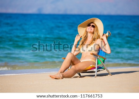 Young beautiful woman on the beach relaxing in the sun