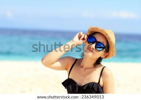Young beautiful woman on the beach, Woman with sunglasses in bikini. #236349013