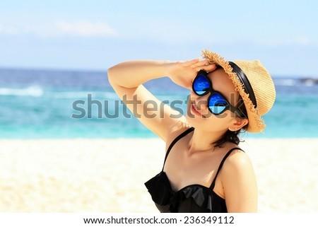Young beautiful woman on the beach, Woman with sunglasses in bikini. #236349112