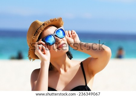 Young beautiful woman on the beach, Woman with sunglasses in bikini, Sunglasses reflects the sun.  #236349067