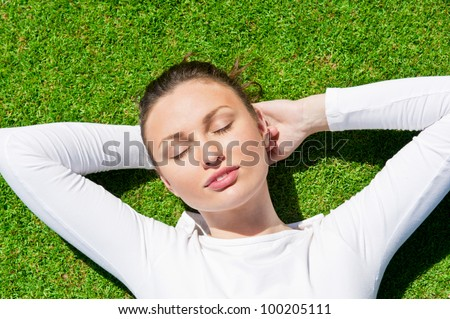 Young beautiful woman on the grass with closed eyes