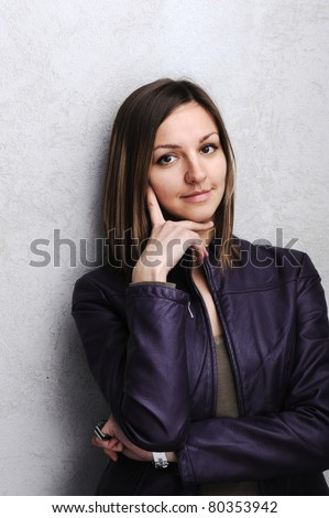 Young beautiful  woman on wall background