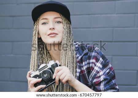 Young beautiful woman photographer is holding the camera and looking into  the camera. She has 0b1d3286a10c