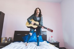 Young beautiful woman playing guitar standing on her bed - girl power, music, having fun concept