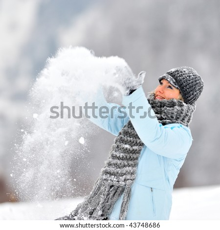 young beautiful woman playing with snow