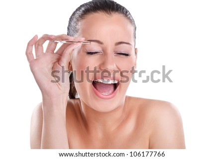 Young beautiful woman plucking her eyebrows with tweezers with a shout of pain