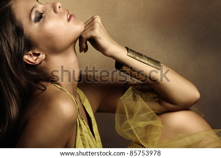 young beautiful woman portrait in golden tones, profile, small amount of grain added, studio shot