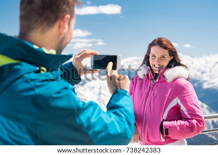 Young beautiful woman posing for a photo in ski resort. Man clicking a picture with smartphone of a girlfriend with snowy mountains in background. Happy couple taking photo of their winter holiday.
