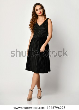 9d8e9e904c5 Young beautiful woman posing in new black fashion winter dress full body on  a white background