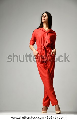 Stock Photo Young beautiful woman posing in new casual red fashion costume dress with pants and hood full body on grey background