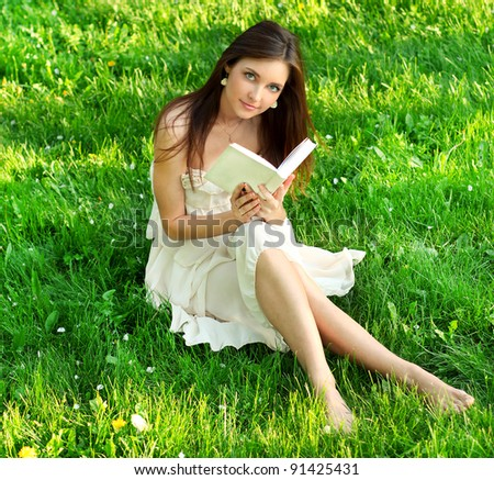 Young beautiful woman reading a book in nature