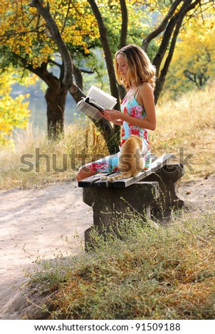 Young beautiful woman reading a book. Near it is the cat against a background of green sunlit nature