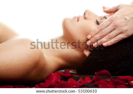 Young beautiful woman receiving a face massage at spa