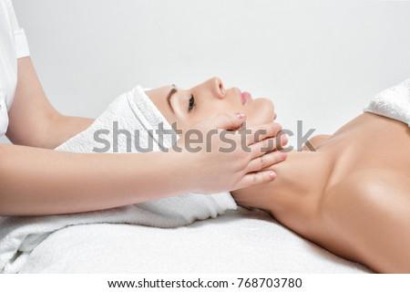 young beautiful woman receiving facial massage at spa salon #768703780