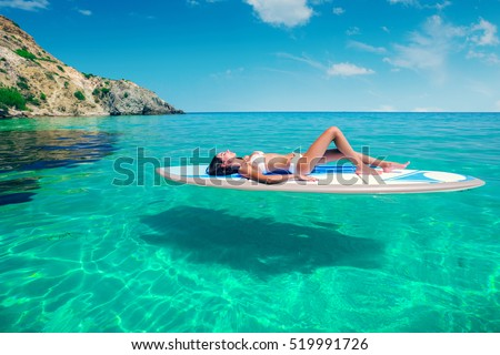 Young beautiful woman relaxing in the sea on a SUP board. The girl sunbathes on the beach of the island on vacation. #519991726