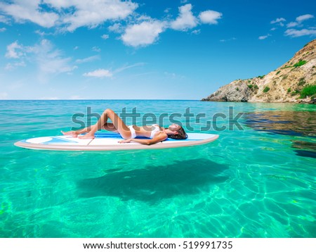 Stock Photo Young beautiful woman relaxing in the sea on a SUP board. The girl sunbathes on the beach of the island on vacation.