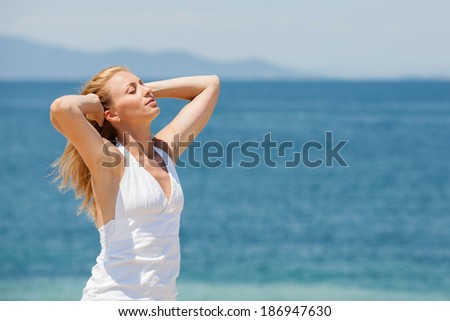 Young Beautiful Woman Relaxing on the beach and reaching for the great sun.