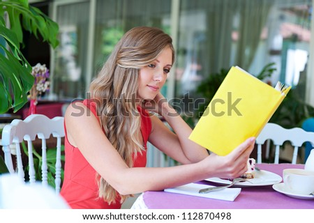 young beautiful woman resting in cafe and reading the book