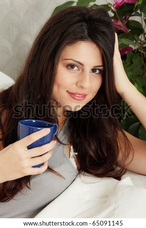 Young beautiful woman resting on sofa with cup of coffee
