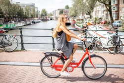 Young beautiful woman riding a bicycle on the bridge over the water channel in Amsterdam old city