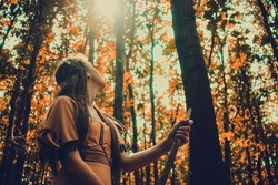 Young beautiful woman scout walking in the woods and looking at the trees, nature preservation concept