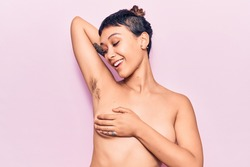 Young beautiful woman shirtless smiling happy. Standing with smile on face showing hairy armpit over isolated pink background