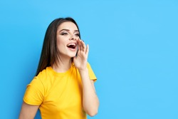 Young beautiful woman shouting and screaming loud to side with hand on mouth and copy space for text on blue background. Attention, communication emotions and advertisement concept
