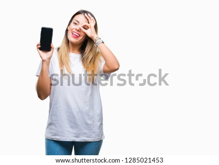 Young beautiful woman showing blank screen of smartphone over isolated background with happy face smiling doing ok sign with hand on eye looking through fingers #1285021453