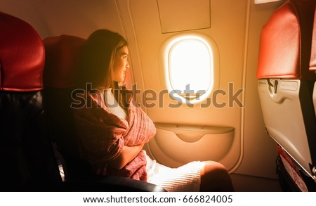 Shutterstock Young beautiful woman sit by window of airplane during flight