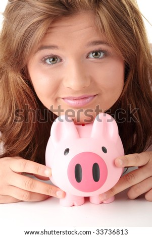 Young beautiful woman siting at the desk with piggy bank (money box), isolated on white background