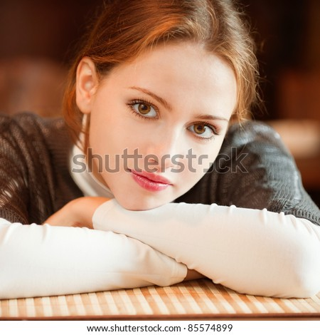 Young beautiful woman sits in cozy cafe and looks.