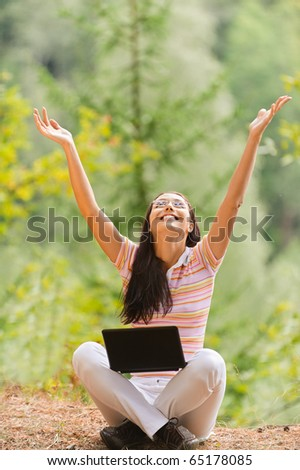 Young beautiful woman sits in pose of lotus with laptop and joyfully lifts hands upwards in summer green park. #65178085
