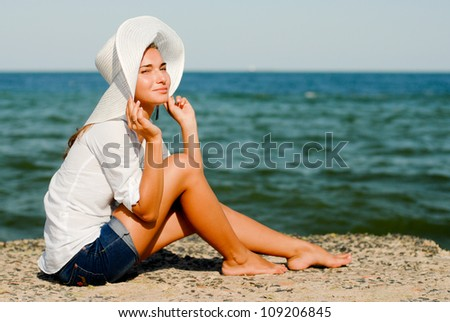 Young beautiful woman sitting by blue sea and wearing white hat