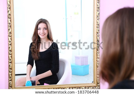Stock Photo Young beautiful woman sitting front of mirror in room
