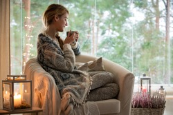 Young beautiful woman sitting home in the chair by the window with cup of hot coffee wearing knitted warm sweater. Cozy room decorated with lanterns and candles. Stay home