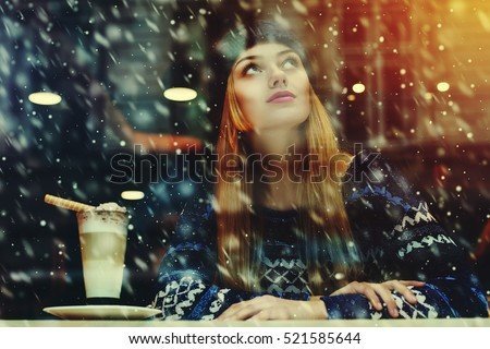 Young beautiful woman sitting in cafe, drinking coffee. Model looking up. Magic snowfall effect. Christmas, new year, winter holidays concept. Waist up. View through the window glass. Toned